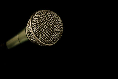 Microphone coming out of darkness with room for ad copy