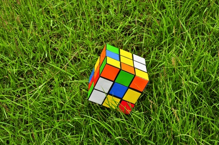 cube puzzle: colorful magic cube on grass Editorial