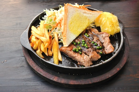 Pork steak with french fries and vegetables  photo