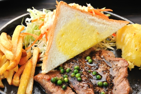 Close up of pork steak with french fries and vegetables Stock Photo - 13074690