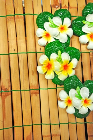 Stone Plumeria craft on bamboo fence, Frangipani  photo