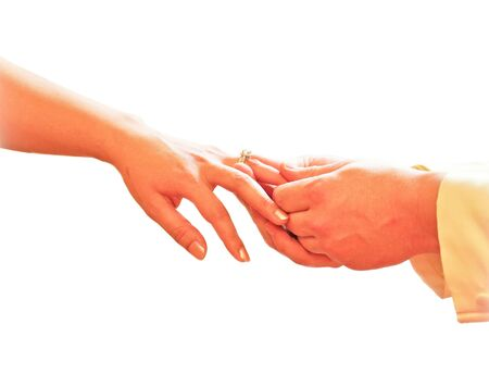 ring finger: Close up of man hand putting a wedding ring on the bride finger, isolate on white background Stock Photo