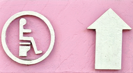 Toilet sign with arrow direction on pink board photo