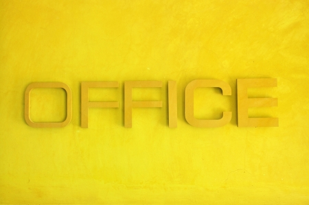 Office text sign on yellow grunge cement wall, textured background  photo