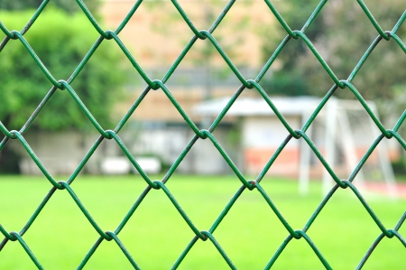 Metal mesh with blur soccer field background