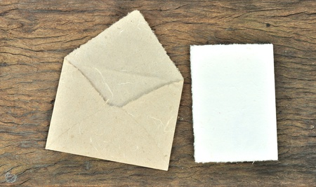 Envelope and blank paper made by Mulberry paper on wooden texture  photo