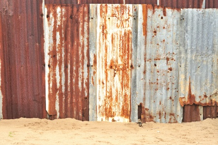 Rusty corrugated metal texture, Zinc fence on sand  photo