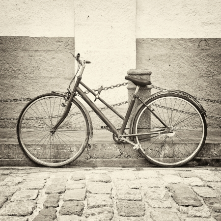 Old bicycle on ancient street in black and white style photo