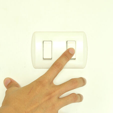 Man hand turn on light switch photo