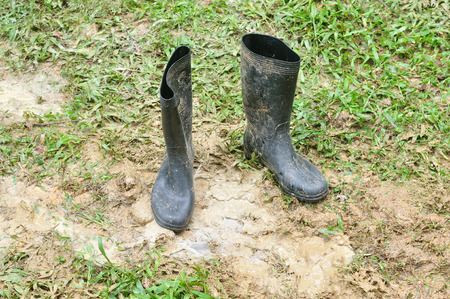 black boots: Black boots in muddy ground Stock Photo