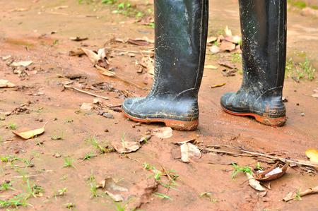 muddy: Black boots in muddy ground Stock Photo