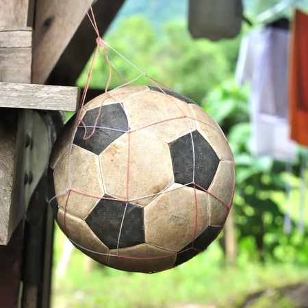 Old football on net in rural scene Stock Photo