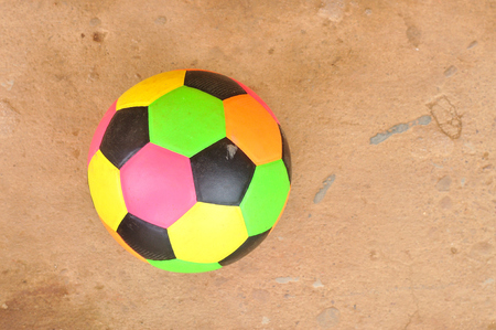 Old colorful football on grunge cement floor