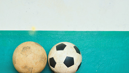 Old footballs with grunge cement wall Stock Photo
