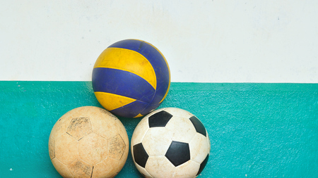 Old footballs and volleyball with grunge cement wall