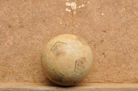 Old football on grunge cement floor
