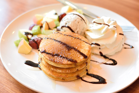 Stack of pancakes with fresh fruits, ice cream and whipped cream Stock Photo