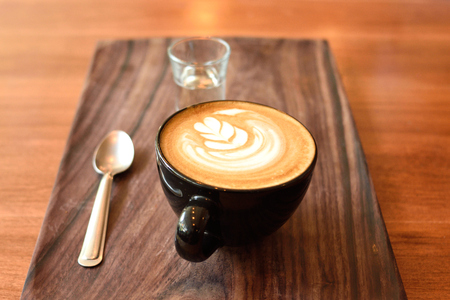 Latte art in coffee shop, Hot coffee on wooden texture Stock Photo