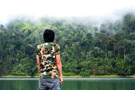 Man take a view of dense tropical rainforest at Rajjaprabha Dam or Cheow Lan Dam (Guilin of Thailand), Forest landscape of Thailand