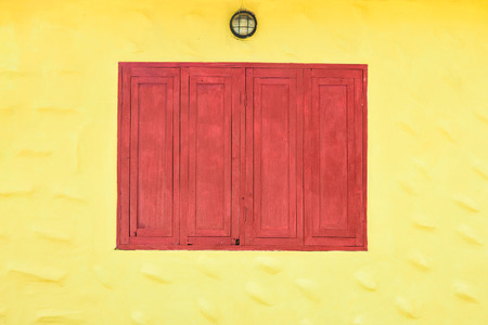 Red grunge wooden window on yellow wall
