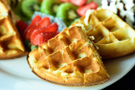 Closeup of waffle with fresh fruits and whipped cream