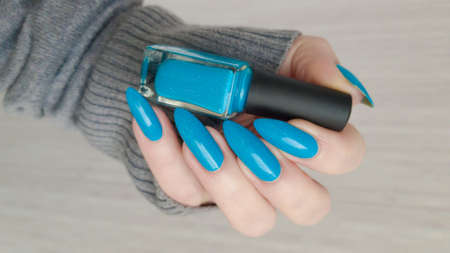 Female hand with long nails and turquoise blue manicure with bottles of nail polish