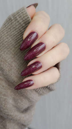 Female hand with long nails and a bottle of dark red nail polish