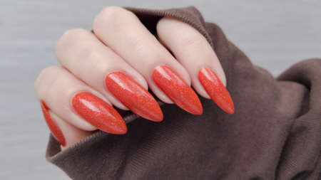 Female hand with long nails and orange ginger manicure holds a bottle of nail polish