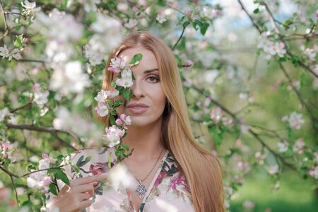 Blond girl with long hair in spring blooming apple orchard