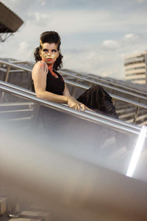Actress woman in a golden mask spikes on her face in a black dress posing near modern buildings urban city Banque d'images