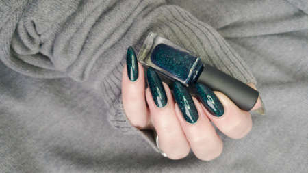 Female hand with long nails and green manicure with bottles of nail polish