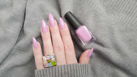 Female hand with long nails and purple lilac manicure holds a bottle of nail polish 免版税图像