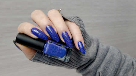 Female hand with long nails and blue manicure with bottles of nail polish
