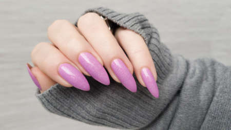 Female hand with long nails and purple lilac manicure holds a bottle of nail polish Фото со стока