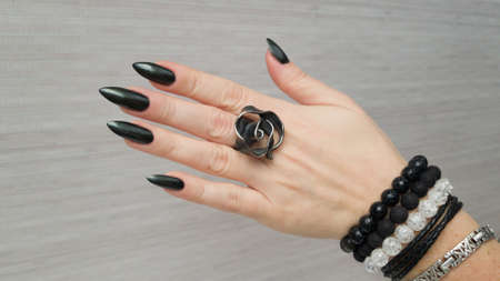 Female hand with long nails and dark, black and gray manicure with bottles of nail polish Фото со стока