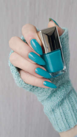 Female hand with long nails and turquoise blue manicure with bottles of nail polish 免版税图像