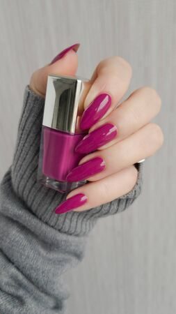 Female hand with long nails and a pink and fuchsia bottle manicure with nail polish