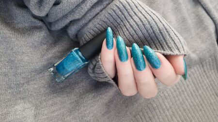 Female hand with long nails and turquoise blue manicure with bottles of nail polish Фото со стока