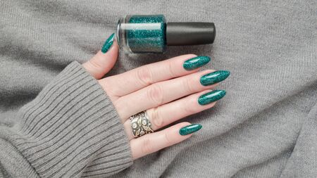 Female hand with long nails and a green manicure holds a bottle of nail polish Фото со стока