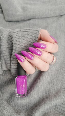Female hand with long nails and pink manicure holding a bottle of nail polish.