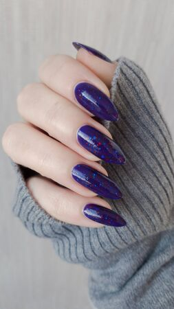 Female hand with long nails and a bottle of purple lilac color nail polish