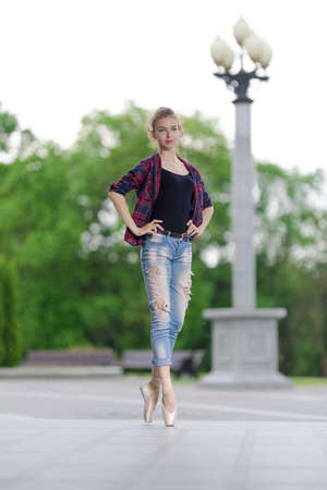Girl ballerina in jeans, a plaid shirt and pointe shoes dancing in the city on the street Banque d'images - 151115081