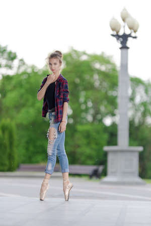 Girl ballerina in jeans, a plaid shirt and pointe shoes dancing in the city on the street Banque d'images - 151115083