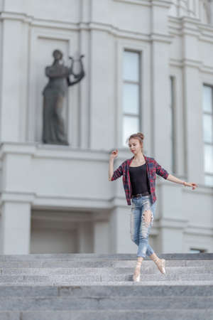 Girl ballerina in jeans, a plaid shirt and pointe shoes dancing in the city on the street Banque d'images - 151122628