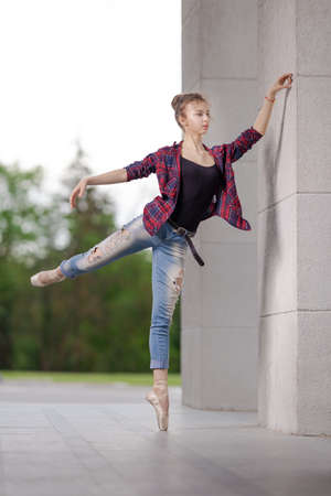 Girl ballerina in jeans, a plaid shirt and pointe shoes dancing in the city on the street Banque d'images - 151115085