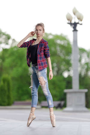 Girl ballerina in jeans, a plaid shirt and pointe shoes dancing in the city on the street Banque d'images