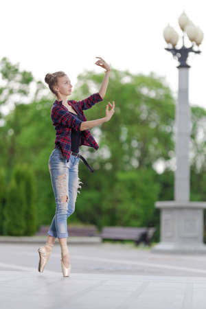 Girl ballerina in jeans, a plaid shirt and pointe shoes dancing in the city on the street Banque d'images - 151115090