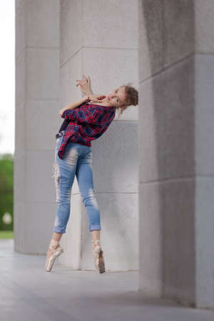 Girl ballerina in jeans, a plaid shirt and pointe shoes dancing in the city on the street Banque d'images - 151115091