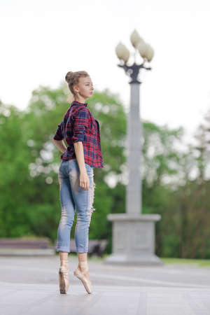 Girl ballerina in jeans, a plaid shirt and pointe shoes dancing in the city on the street Banque d'images - 151115092