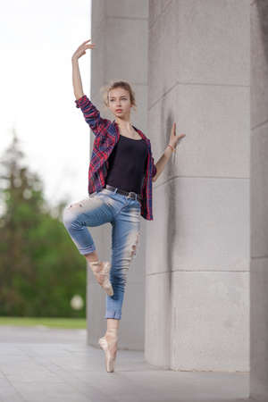 Girl ballerina in jeans, a plaid shirt and pointe shoes dancing in the city on the street Banque d'images - 151122633